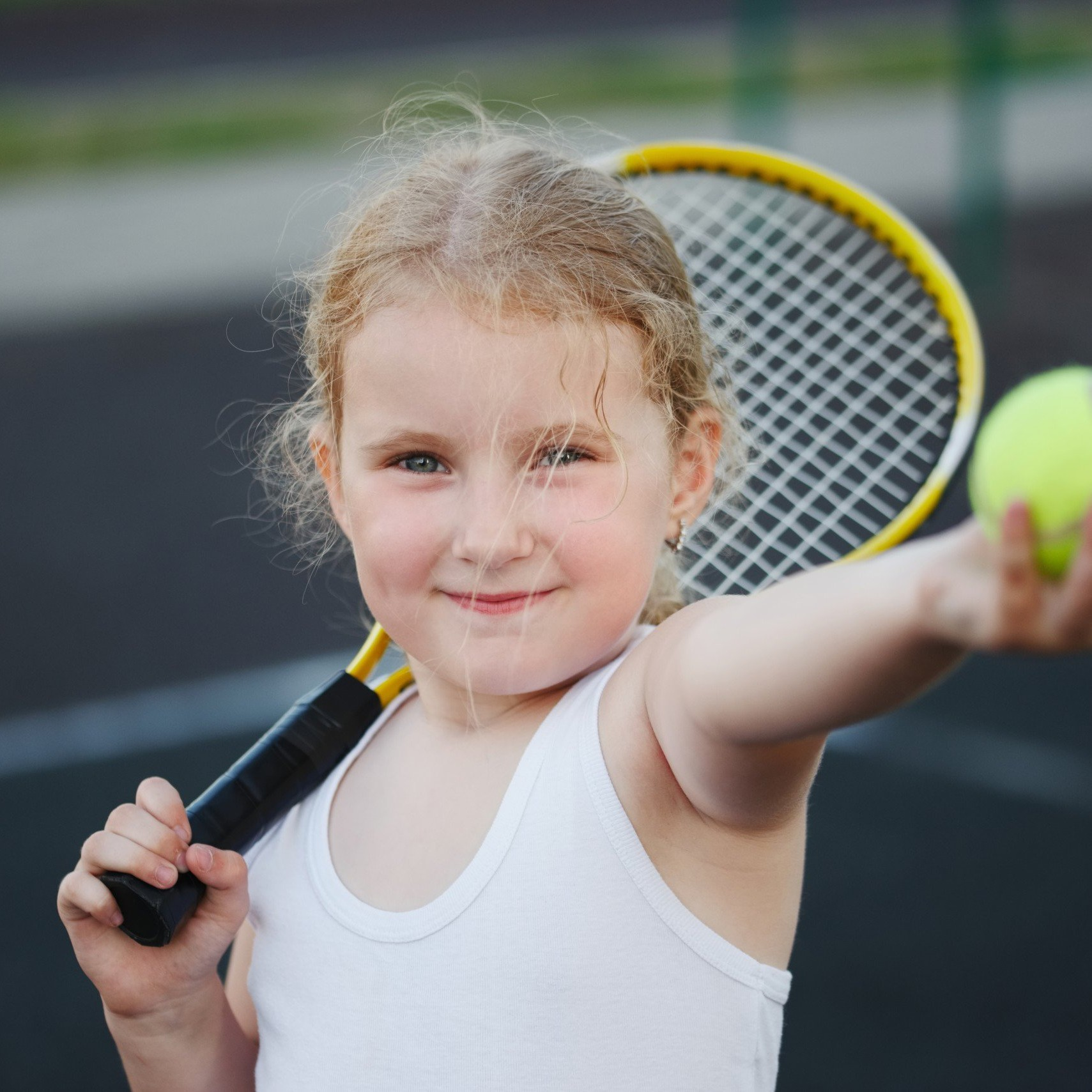 little girl plays tennis on court outdoors